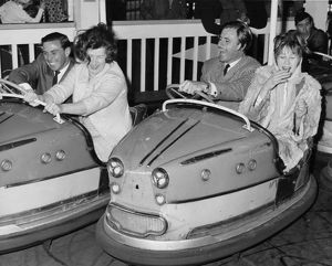 Racing drivers Graham Hill and Jim Clark enjoying a dodgem ride